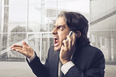 angry boss: Angry businessman screaming on the mobile phone