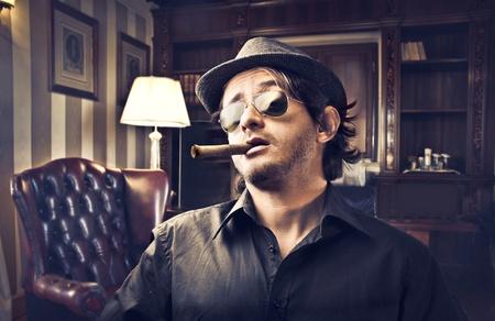 Jefe de joven fumando un cigarro en un estudio de lujo