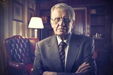 Serious senior businessman in a luxury studio photo