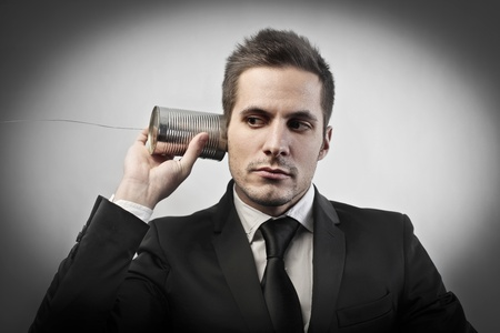 stupor: Businessman using a can with a rope as a telephone