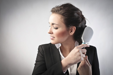 buisness: Young businesswoman brushing her hair