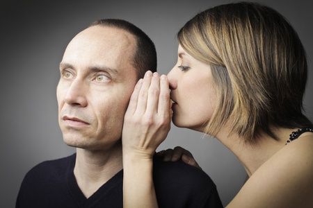 Young woman telling an astonished man a secret Stock Photo - 12648789