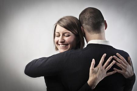 friend hug: Smiling woman hugging her husband
