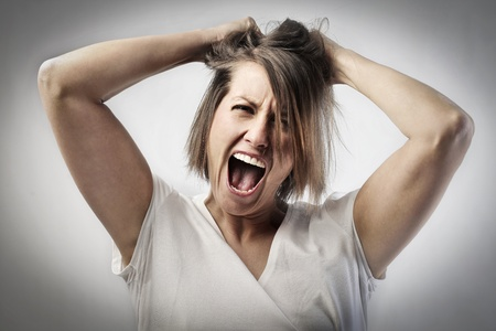 crazy: Furious woman screaming and pulling her hair Stock Photo