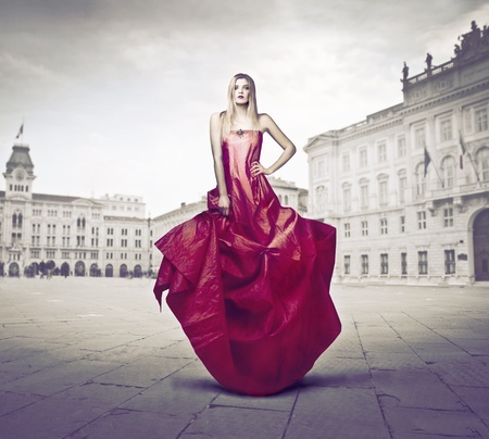 evening gown: Beautiful elegant woman wearing an evening gown on a town square