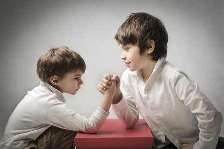 standoff: Two children playing arm wrestling