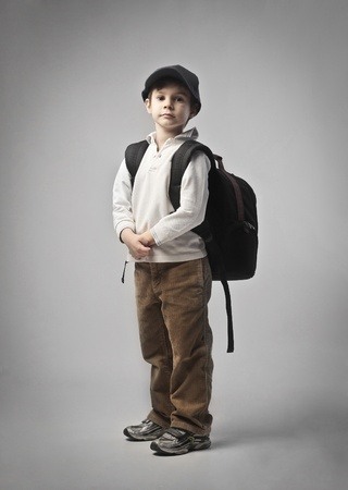 Child carrying a backpack on his shoulders photo