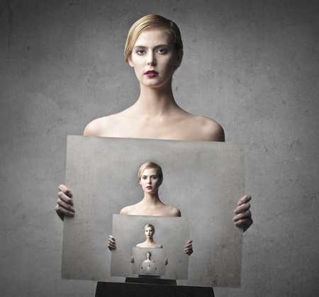 innumerable: Beautiful woman holding a picture of her holding a picture of her to infinity Stock Photo