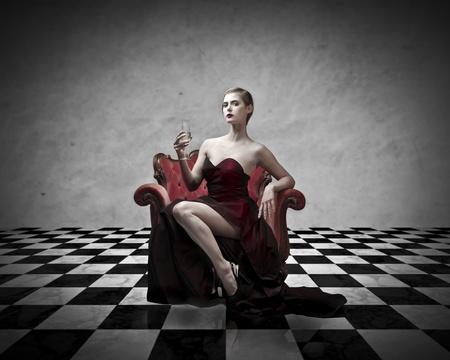 coupe de champagne: Belle femme riche, assis sur un fauteuil et tenant un verre de champagne