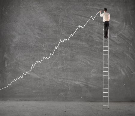 enterprises: Young businessman on a ladder charting a positive trend graph