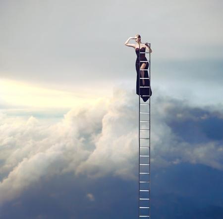mooie vrouwen: Mooie elegante vrouw op een ladder op zoek ver weg Stockfoto