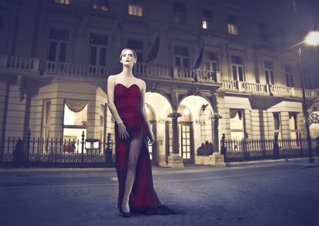leave: Beautiful woman wearing an evening gown with luxury building in the background