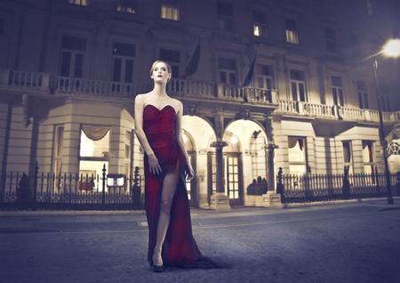 luxe: Belle femme portant une robe de soir�e avec la construction de luxe dans l'arri�re-plan Banque d'images