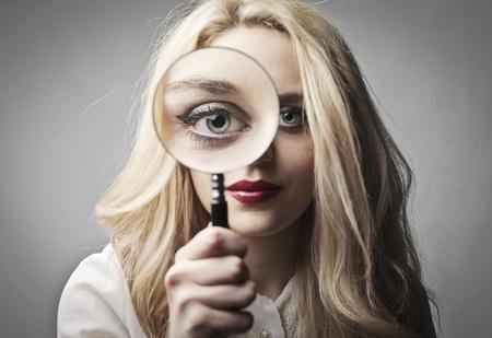 lupa: Krásná žena drží zvětšovací sklo Reklamní fotografie