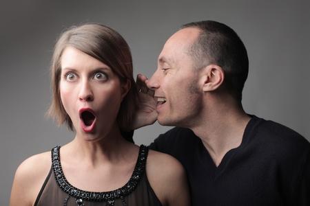 listen ear: Man telling an astonished woman a secret