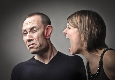 ironic: Furious woman screaming against her husband with his face deformed by the shrilling shouts Stock Photo