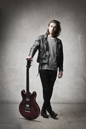Young man in leather jacket holding a guitar photo