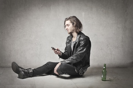 rocker: Young man in leather clothes uaing a mobile phone with a beer bottle beside him Stock Photo