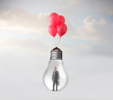 Businessman in a light bulb flying with some balloons Stock Photo - 13010569