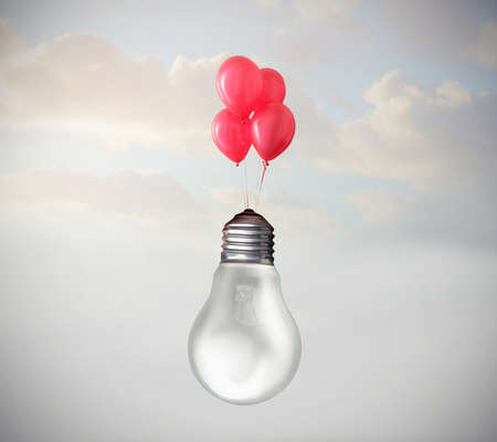 Light bulb flying with some balloons Stock Photo