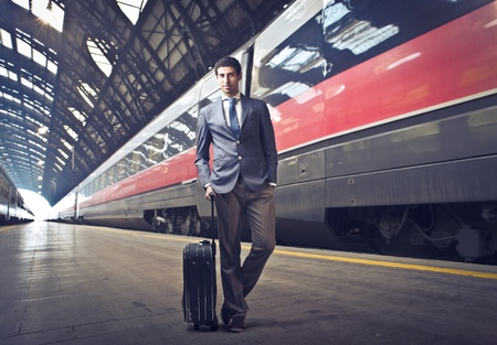 Young businessman standing on the platform of a train station photo