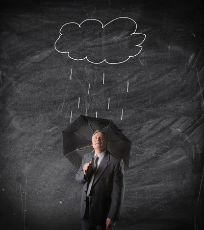 Sad senior businessman under n umbrella with drawn raincloud on a blackboard in the background photo