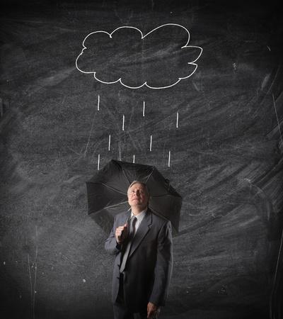 weather beaten: Sad senior businessman under n umbrella with drawn raincloud on a blackboard in the background