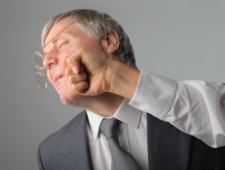 punched: Senior businessman being punched in his face