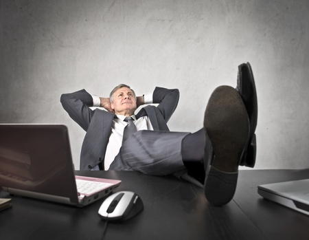 Senior businessman relaxing at the office with his feet on the table photo