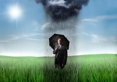 Sad Senior Geschäftsmann unter einem Regenschirm auf einer grünen Wiese mit Regenwolke über ihn und sonnigen Himmel im Hintergrund