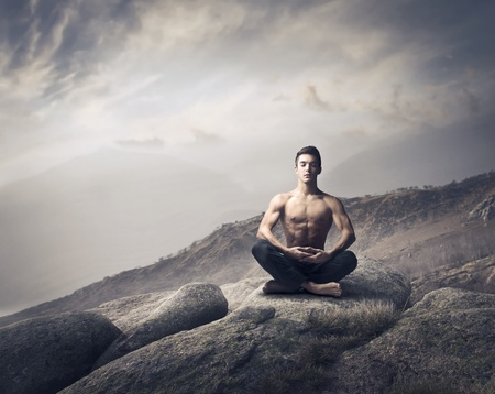 yoga rocks: Handsome bare-chested young man sitting on a mountain peak and meditating