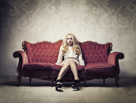 Beautiful rich woman sitting on a velvet sofa photo