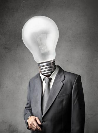 head light: Hombre de negocios con una bombilla de luz en lugar de la cabeza Foto de archivo
