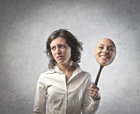 hipocres�a: Triste mujer joven posponiendo una m�scara de expresi�n de la alegr�a