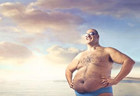 지방: 해변에서 중량이 초과 된 사람이 웃고