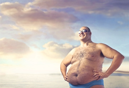 Smiling overweight man at the seaside