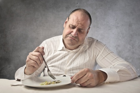 ugly man: Sad fat man eating some vegetables Stock Photo