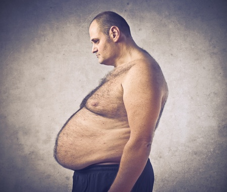 paunch: Profile of a disappointed  overweight man looking at his belly