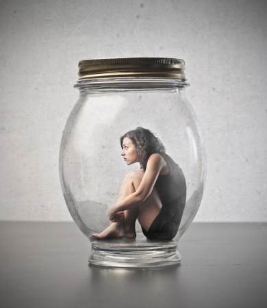 traps: Young woman trapped in a glass jar