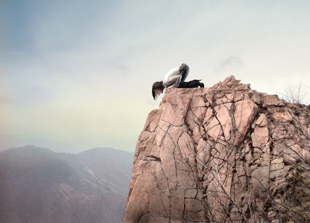 downwards: Young businesswoman kneeling on a dangerous peak and looking downwards