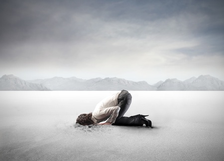 head in the sand: Young businesswoman burying her head in the sand
