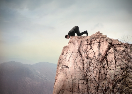fear of failure: Young businessman kneeling on a dangerous peak and looking downwards Stock Photo