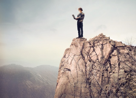 Young man standing on a mountain peak and using a laptop photo