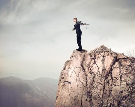parapente: Joven empresario abriendo los brazos para volar desde un pico de montaña