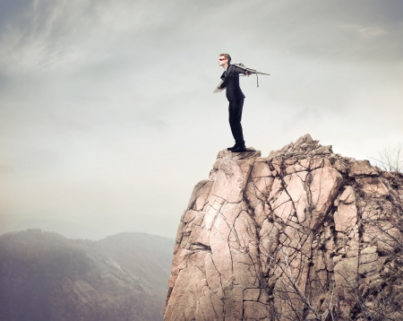 paragliding: Young businessman spreading his arms to fly from a mountain peak Stock Photo