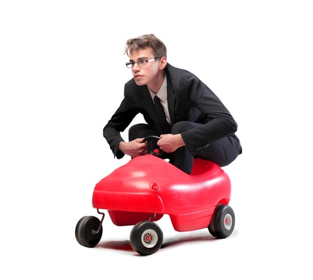 ironic: Isolated young businessman driving a toy car