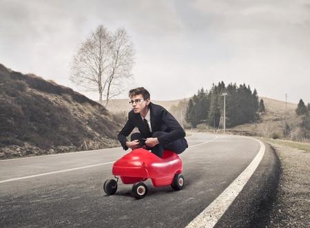 국가 도로에 장난감 자동차를 운전하는 젊은 사업가
