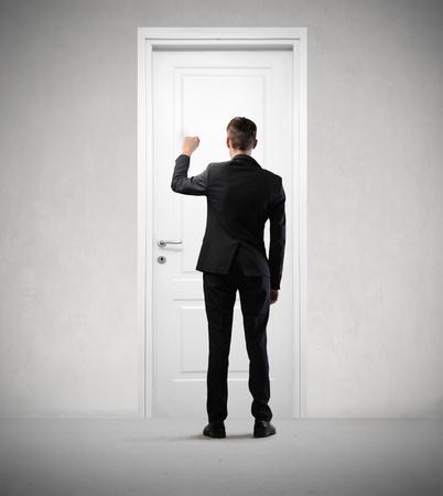 puertas de madera: Joven empresario llamando a una puerta Foto de archivo