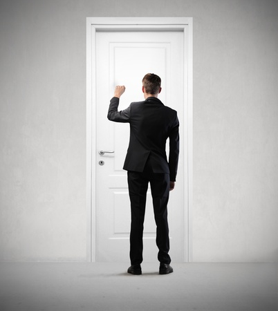work material: Young businessman knocking at a door Stock Photo