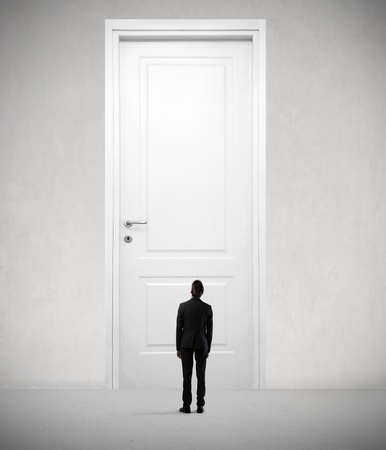 Tiny businessman standing in front of a giant door photo